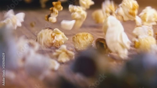 Fresh fluffy popcorn falling on authentic wooden table - super slow motion shot