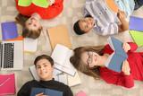 Group of teenagers doing homework on floor
