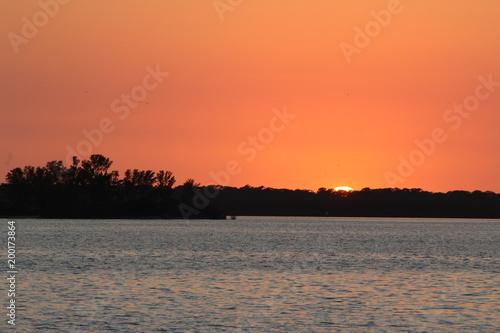 Foto op Plexiglas Oranje eclat Orange sky after the sun is below the horizon with calm water