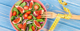 Fresh prepared fruit and vegetable salad, fork with tape measure, healthy lifestyle, slimming and nutrition concept