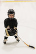 Adorable little kid 3 years-old plays hockey on ice wearing in full hockey equipment