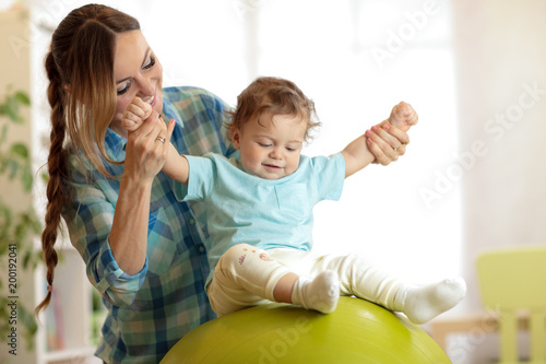 Happy mother and baby toddler on fitness ball in nursery at home. Gimnastics for kids on fitball. - 200192041