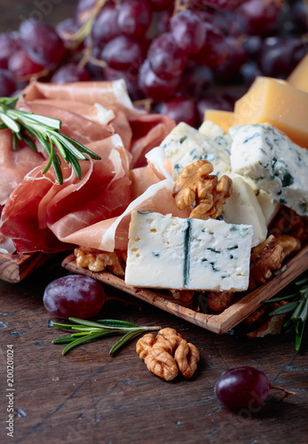 Foto Murales Prosciutto with various cheeses , grapes and  walnuts .