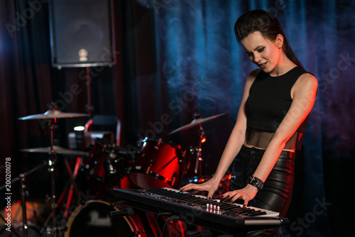 Woman playing keyboard on dark stage - 200201078