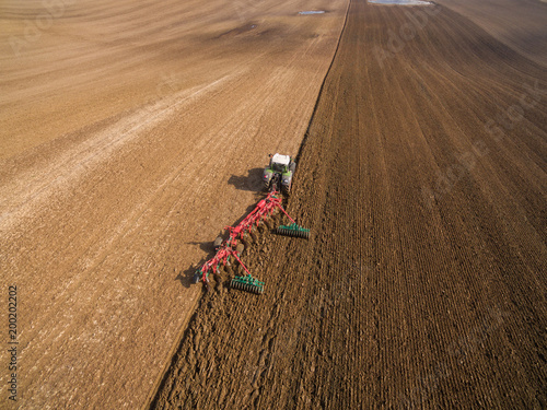 Fotobehang Trekker Tractor plows a field in spring -Tractor cultivating a field - Aerial view
