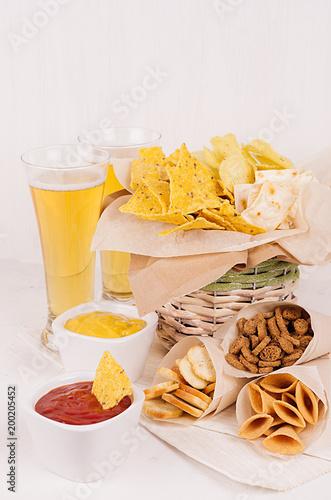 Letnia fast food - różne chrupiące przekąski i czerwony, żółty sos w białych miseczkach, zimne piwo na miękkiej białej desce, pionowe.