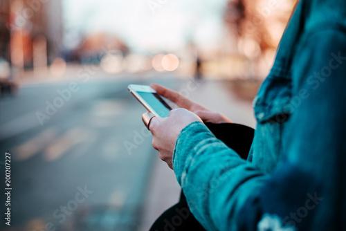 Using phone at city street. Close-up.