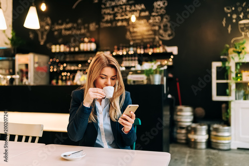 Beautiful woman drinking coffee and using phone at the restaurant.