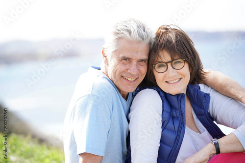 Foto Murales Portrait of cheerful 60-year-old couple relaxing by the sea