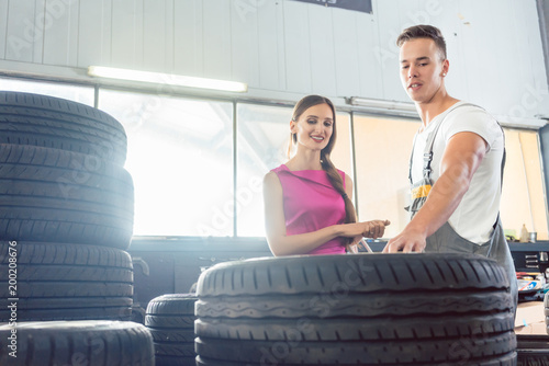 Handsome auto mechanic helping a female customer to choose from various high-quality tires in a contemporary automobile repair shop