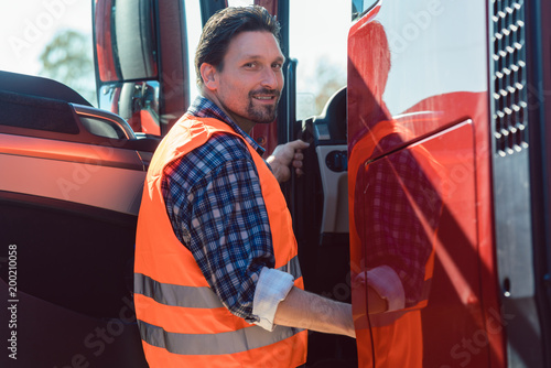 Fridge magnet Truck driver in front of his freight forward lorry looking at camera