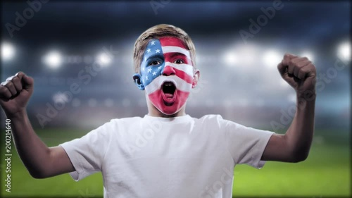 Boy with the Brazilian flag painted on his face yelling goal