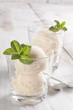 Vanilla ice cream cups with mint leafs.