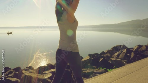 Woman stretching after jogging in front of lake at sunset