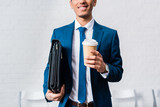 Smiling businessman holding briefcase and coffee cup - 200225629