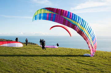 Ringstead Bay, Dorset / England. 02/15/2018. Paragliding pilots riding the wind off the cliffs of the Dorset Coast in training for the British Open Competitions in July.