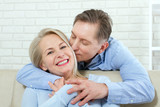 Close up photo of cheerful excited happy happily happy with toothy shining smile blond attractive woman and man, he hugs her from behind and kisses - 200228826