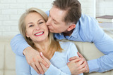 Close up photo of cheerful excited happy happily happy with toothy shining smile blond attractive woman and man, he hugs her from behind and kisses - 200228836