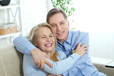 Happy couple in love hug each other on bed at home - 200228882