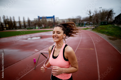 Aluminium Hardlopen Portrait of attractive young happy fitness girl jogging on a track while listening to music near the soccer field.