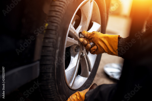 Auto mechanic man with electric screwdriver changing tire outsid - 200235097