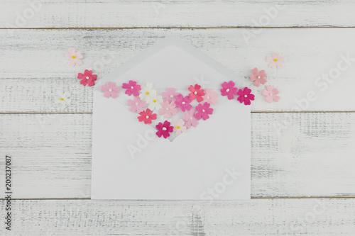 Biała koperta dekoruje z różowymi papierowymi kwiatami na białym drewnianym tle