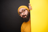 Bright expressive hipster behind yellow banner