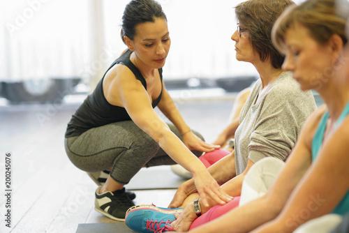 Grupa starsi ludzie w sprawność fizyczna pokoju ćwiczy z trenerem