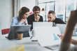 Brainstorming process at sunny office.Young coworkers work together modern office studio.Happy business team making conversation.Horizontal.Blurred background.
