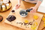 Woman adding chocolate into yoghurt - 200260625