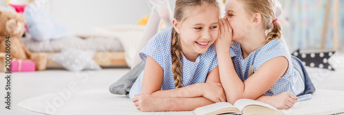 Girl whispering joke to sister