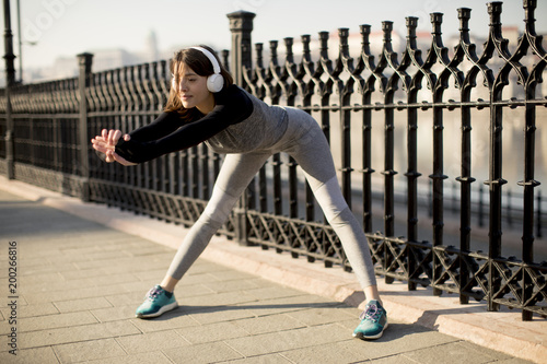 Foto op Plexiglas Jogging Young woman practices stretching after jogging outdoor