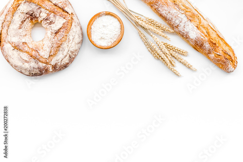 Appetizing fresh bread concept. Baguette and round loaf near ears of wheat on white background top view copy space