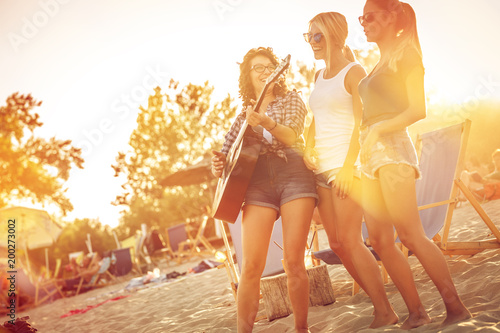 Group of young female friends  on beach  singing and playing guitar.Joying in sunset.