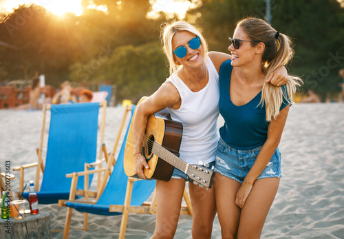 Two young female friends hangout at the beach ,singing and relaxing in beautiful summer sunset.They hug each other.