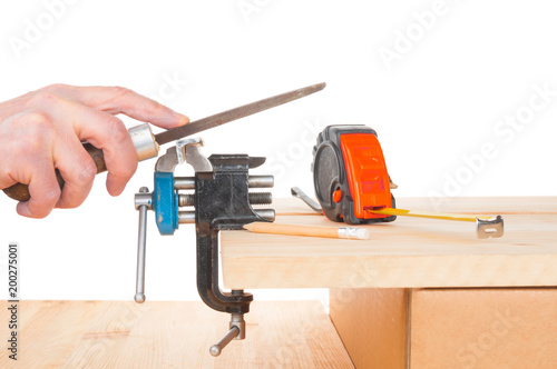 Male hand with rasp working at vise bench on white background