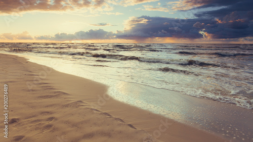Foto Murales Beatiful sunset with clouds over sea and beach