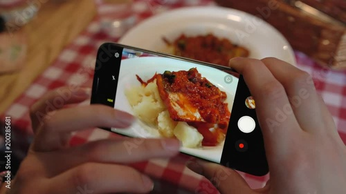 Girl makes a photo of meal on a smartphone in a cafe close up