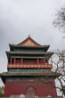Beijing, China - April 26, 2010: Short side of upper structure of Drum Tower shows maroon, green and gold colors under gray sky. Some tree in photo.