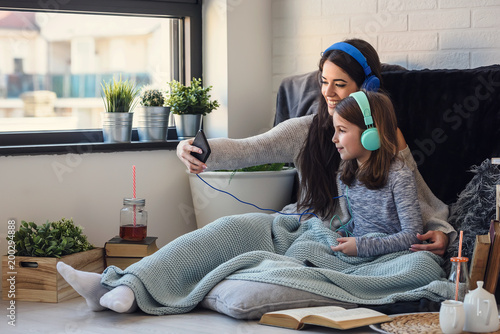 Girls having fun at home, listening music over smart phone. Family quality time