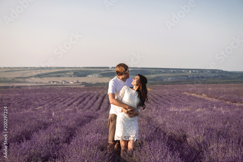 Beautiful young coulpe walking against lavender fields and hills. - 200297224