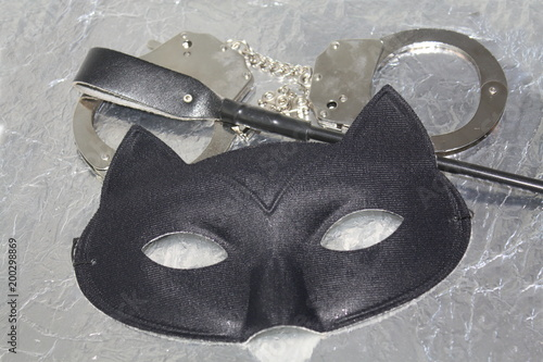 Mysterious erotic pleasure things concept. Cat eye mask, whip and hand cuffs. Fetish role playing. - 200298869