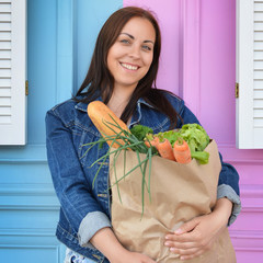 Girl in a jeans jacket is holding a paper bag with food in her hands. The woman stinted in the supermarket. Crafting. Baguettes. Leaves of lettuce. Carrot.