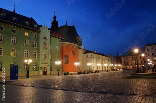 Nocny widok Małego Rynku w Krakowie, Polska, zabytkowa architektura, ludzie odpoczywający na ławkach, uliczne lampy, ciemnogranatowe niebo