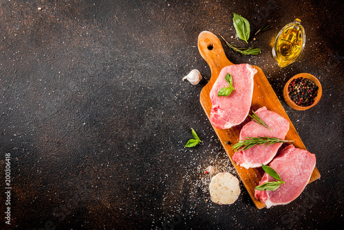 Fotobehang Steakhouse Raw meat, pork steaks with spices, herbs, olive oil, dark background top view, copy space