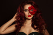 Portrait of beautiful sexy woman with creative makeup and red rose petals of her face