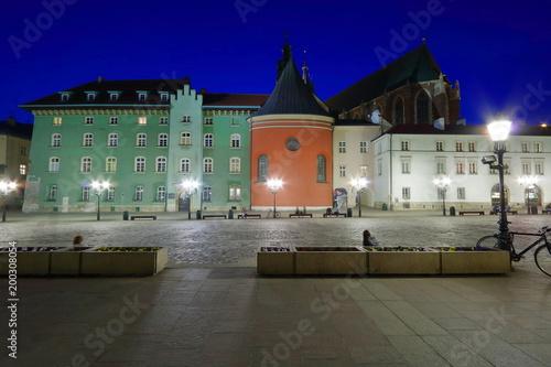 Foto op Plexiglas Krakau Mały Rynek w Krakowie, Polska, nocny widok, zadbane zabytkowe kamienice, dach bazyliki mariackiej w tle, świecą uliczne lampy, ludzie relaksują się na ławkach, piękne ciemnoniebieskie niebo