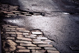 Old New York City cobblestone street repaired with asphalt