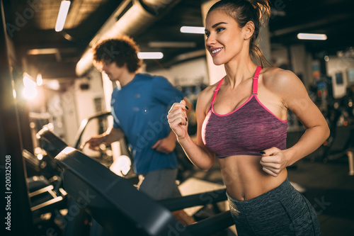Horizontal photo of attractive woman jogging on treadmill at health club. © GutesaMilos