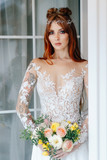 portrait of a cute red-haired bride with a bouquet in hands